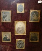 A quantity of Victorian portrait photographs housed in a common frame. 44 x 53 cm.