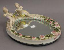 A Continental porcelain mirror surmounted with cherubs. 31.5 cm high.