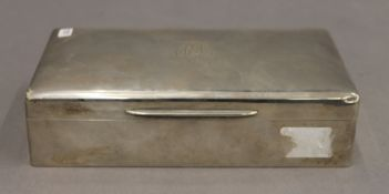 A silver cigarette box. 18 cm wide. 12.2 troy ounces total weight.