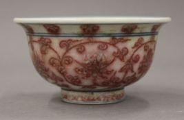 A Chinese porcelain tea bowl with red floral decoration. 9.5 cm diameter.