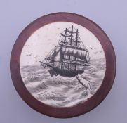 A wood and bone box decorated with a ship. 6.5 cm diameter.