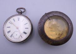 A silver pocket watch. 6 cm wide.