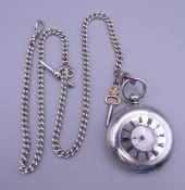 A silver half hunter key wind pocket watch, with silver Albert chain. 4.6 cm diameter.