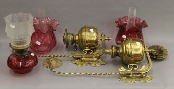A pair of wall mounted brass oil lamps with cranberry shades and another.