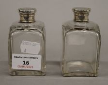 A pair of Edwardian silver topped cut glass perfume bottles. 8.5 cm high.
