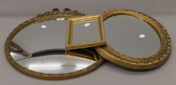 A gilt framed convex wall glass and five other gilt framed wall glasses.