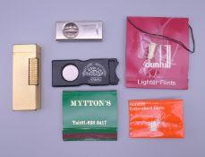 A Dunhill plated lighter, etc. 6.5 cm high.