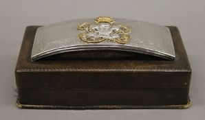 A leather cigarette box with silver military mount. 22 cm wide.