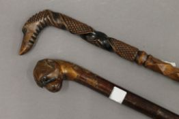 Two dogs head carved wooden walking sticks. The largest 90 cm high.