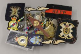 A collection of various militaria, including cap badges, buttons, medals, etc.