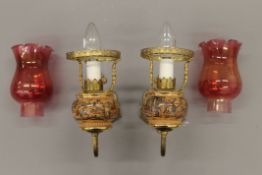 A pair of wall lights with cranberry glass shades. 24 cm deep.