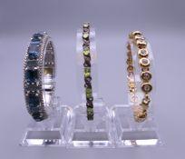 An Art Deco style blue stone bracelet, a sterling silver green stone bracelet and another bracelet.