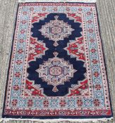 A Pakistani hand knotted blue ground rug. 195 x 130 cm and 194 x 128 cm, respectively.