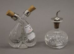 A silver topped salad dressing bottle and a silver mounted double vinaigrette bottle.