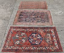 A red ground wool rug and two wool rugs. The former 180 x 100 cm.