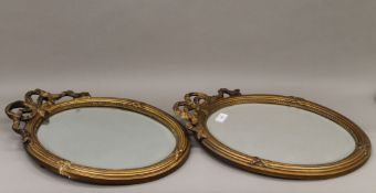 A pair of gilt framed wall glasses, each with bevelled mirror plate. 50 cm high.