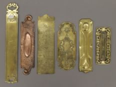 A collection of antique brass fingerplates. The largest 41.5 cm high.