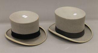 Two grey felt top hats.