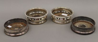 Two pairs of silver plated bottle coasters. The largest 14.5 cm diameter.
