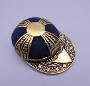 A pin cushion in the shape of a jockey cap. 4 cm wide.