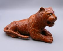 A carved wooden model of a tiger. 14 cm long.