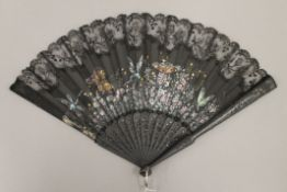 A boxed painted black lace fan. 24 cm high.