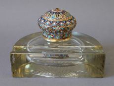 A glass inkwell set with an enamel decorated silver gilt lid, bearing Russian marks. 15.5 cm wide.