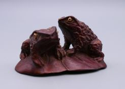 A Japanese wood netsuke of two frogs. 5.5 cm wide.