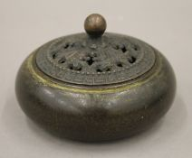 A Chinese bronze censer with pierced lid. 10 cm diameter.