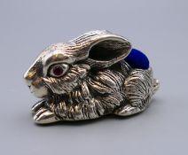 A silver rabbit form pin cushion. 5 cm long.