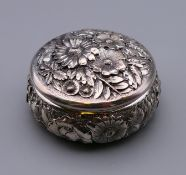 A sterling silver circular embossed pill box. 5.5 cm diameter.