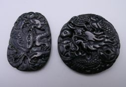 Two carved jade pendants. The largest 4.75 cm high.