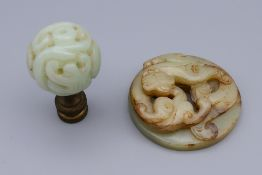 A carved jade roundel and a carved jade finial. The former 5 cm diameter.