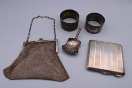 A silver compact, two silver napkin rings, a mesh purse and part of a caddy spoon.