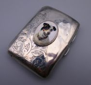 A silver cigarette case decorated with a dog. 7.5 cm high.
