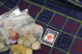 A quantity of vintage casino chips and a vintage casino Roulette tablecloth.