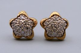 A pair of 9 ct gold diamond star shaped cluster earrings. 1 cm diameter. 1.8 grammes total weight.
