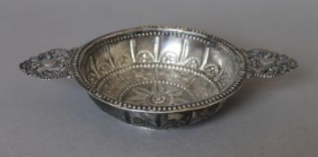 An embossed unmarked silver twin handled dish. 21.5 cm wide. 190.6 grammes.