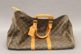 A Louis Vuitton holdall. 45 cm wide.