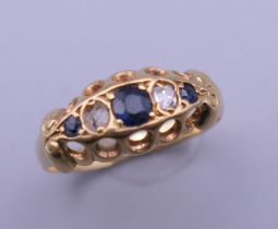 An 18 ct gold diamond and sapphire ring. One diamond missing. Ring size M. 2.3 grammes total weight.