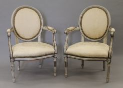 A pair of upholstered 19th century painted open armchairs. 59 cm wide.