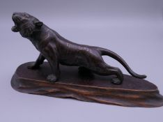 A Japanese bronze model of a tiger, on a wooden base. The tiger 13 cm long.