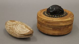 An Indonesian woven circular box the lid inlaid with mother-of-pearl and mounted with wooden fish,