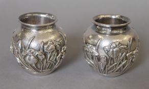 A pair of Japanese embossed silver vases, with Liberty & Co import marks. Each 6.5 cm high. 247.