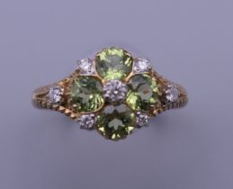 A 9 ct gold, peridot and diamond ring, with engravings to the sides. Ring size M/N.