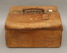 A Drew & Co crocodile skin travelling bag, containing some silver mounted accessories. 39 cm wide.