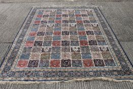 A deep blue ground full pile Kashmir carpet with all over Persian panel design. 380 x 280 cm.