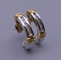 A pair of 18 ct yellow and white gold half hoop diamond earrings, with 18 ct gold butterfly clips.
