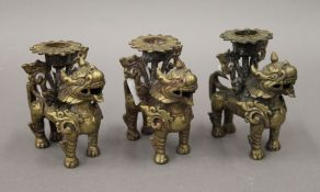 Three Chinese bronze dog-of-fo form candlesticks. 9 cm high.