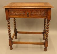 A Victorian carved oak single drawer barley twist side table. 67.5 cm wide.